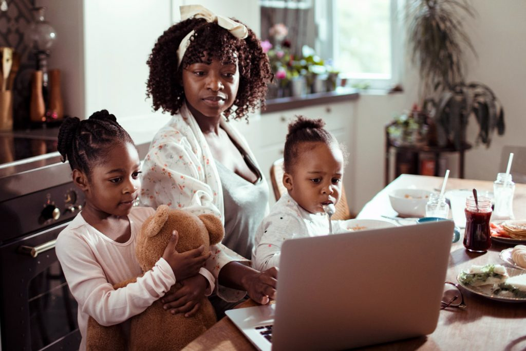 A mother works on a laptop with her two daughters next to her.