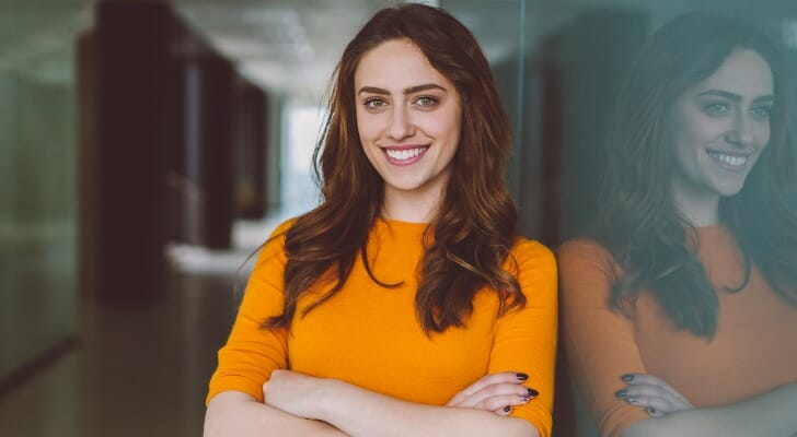 Image shows a person wearing business casual clothing and standing against an office wall with her arms crossed. In this study, SmartAsset analyzed data to identify the most in-demand jobs for bachelor's degree holders.